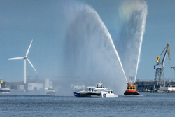 A boat is sailing with a windmill in the background and a fireboat throwing water at it