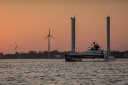 Energy Observer with sunset and wind turbines in the background