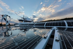 View of the boat and its solar panels and vertical wind turbines