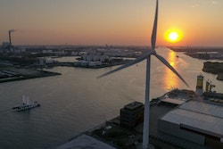A drone image with a wind turbine in the foreground and Energy Observer navigating in Amsterdam in the background