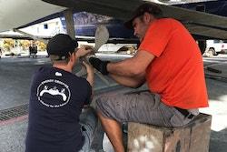 Deux membres d'équipage retirent les hélices à pas variables du bateau