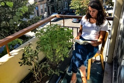 A woman reading a book on a balcony