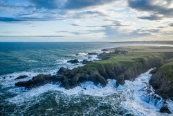 Drone picture of a cliff and rough sea near Abderdeen, Scotland