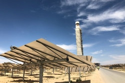Solar panels with a tower in the background in the middle of the desert