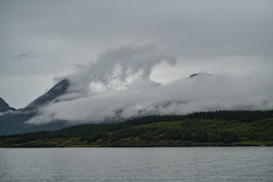 Picture of mountains close to the sea with clouds