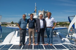 4 people pose for a picture on the central nacelle of the boat