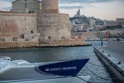 Energy Observer moored with the Old Port of Marseille in the background