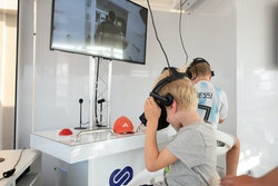 Two little boys look into virtual reality helmets