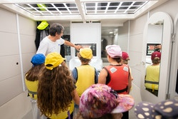 An engineer points out the monitoring in the boat to the children at the air centre