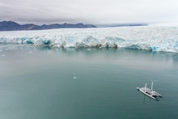 Drone view from behind of Energy Observer near a glacier