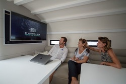 Three people are looking at a screen in the boat