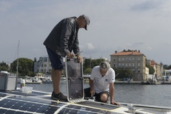 Two people work on the solar panels