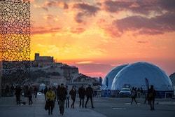 Le village d'Energy Observer avec un coucher de soleil et des passants