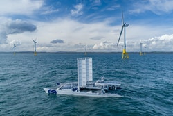 Energy Observer in front of sea wind turbines